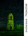 Old abandoned orthodox church under clear night sky with star trails, long exposure