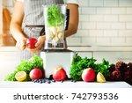 woman blending lettuce leaves ... | Shutterstock . vector #742793536