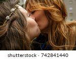 Small photo of A daughter and her mother kiss affectionately on the cheek, in a very affectionate gesture