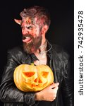 Small photo of Devil or monster with October decorations. Man wearing scary makeup holds pumpkin on black background. Demon with horns and cheeky face showing tongue holds jack o lantern. Halloween party concept
