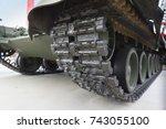 view of the front part of the green caterpillar of the tank standing on the ground with the wheels close-up.