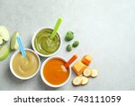 bowls with baby food on grey... | Shutterstock . vector #743111059