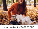 Stock photo young beautiful red haired girl in a fashionable orange sweater is walking with her dog in the park 743239006