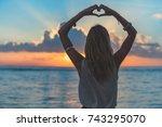girl holding a heart shape on... | Shutterstock . vector #743295070