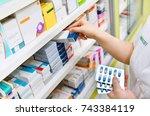 pharmacist holding medicine box ... | Shutterstock . vector #743384119