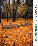 Small photo of Two old empty broken benches in an autumn park and yellow leaves all around