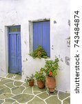 Small photo of paved alley and colorful old traditional stone houses in the Aegean island, Cyclades, Greece