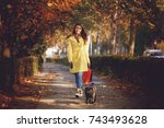 Stock photo young woman walking with a dog after shopping 743493628