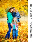 Small photo of happy family in a beautiful autumn park, amicably hug and smile