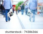 People in rush in a modern shopping mall. Close up and reflection of a man walking - stock photo