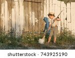 Stock photo pretty boy in the straw hat as tom sawyer in front of fence with the shadow the boy paint a wooden 743925190
