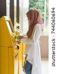 Small photo of muslim woman withdraw money