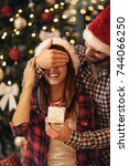 couple with christmas surprise  | Shutterstock . vector #744066250