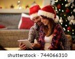 christmas couple celebrating... | Shutterstock . vector #744066310