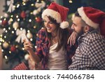 young pair in love at christmas ... | Shutterstock . vector #744066784