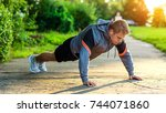 male athlete exercising in park.... | Shutterstock . vector #744071860