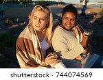 intercultural girls with drinks ... | Shutterstock . vector #744074569