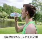 young sportsman drinks water... | Shutterstock . vector #744111298