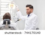 cheerful young male dentist... | Shutterstock . vector #744170140