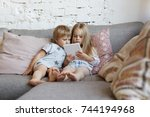 elder sister relaxing on couch... | Shutterstock . vector #744194968