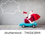 santa claus riding car.... | Shutterstock . vector #744261844
