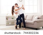 young couple dancing at home ... | Shutterstock . vector #744302236