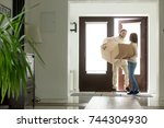 Small photo of Happy young couple carrying cardboard boxes opening door entering inside modern own house, excited married family property owners moving in into new home, buying real estate, mortgage loan