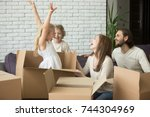 Small photo of Happy child girl jumping out of cardboard box, family playing with kids in living room on sofa, parents and children laughing having fun together at moving day, move in new home or relocating concept