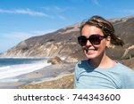 Small photo of A brunette woman smiles while visiting Big Sur along the California State Route Highway 1, along the pacific ocean.