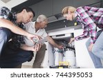 Small photo of A woman shows plumbers a broken kitchen sink. One of the men inspects the pipes, the second one writes on the tablet. The woman shows the place of breakage.