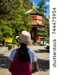 Small photo of Girl with backpack entering to Quan Yin Shrine at Wat Tham Seua (Tham Seua Temple) Krabi, Thailand.