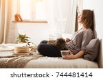 Stock photo young woman with a cat lying in bed at home winter or autumn weekend concept woman reading book 744481414
