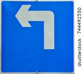 Small photo of Direction left arrow blue sign
