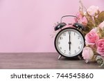alarm clock and rose on wood... | Shutterstock . vector #744545860