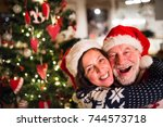 senior couple with santa hats... | Shutterstock . vector #744573718