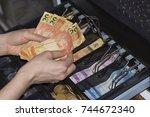 saleswoman hands at cash... | Shutterstock . vector #744672340