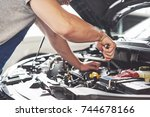 auto mechanic working in garage.... | Shutterstock . vector #744678166