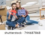 young happy couple sitting on... | Shutterstock . vector #744687868