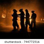 Silhouettes Of Firemen Fightin...