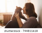 Stock photo young woman playing with cat in home 744811618