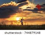 boy launch a kite in the field... | Shutterstock . vector #744879148