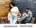 woman watching smartphone while ... | Shutterstock . vector #744927040