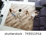 Small photo of Family playing hide and seek game at home, mother and kids hiding clapping hands while blindfolded father seeking catching children wife, parents and son daughter having fun in living room, top view