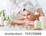 girl lying down on a massage bed | Shutterstock . vector #745150888