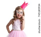 Small photo of Funny princess girl in pink dress and crown holding party glasses on stick