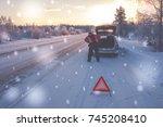 broken car on a snowy winter... | Shutterstock . vector #745208410
