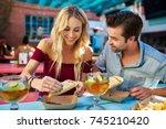 romantic couple eating street... | Shutterstock . vector #745210420
