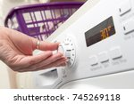 hand adjusting the temperature... | Shutterstock . vector #745269118