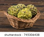 Small photo of Sweet And Healthy Fruit Custard Apple Also Know as Sitafal, Sweetsop, Annona Squamosa, Sugar Apple, Sitaphal or Anona in Basket on Wooden Table