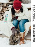 Stock photo portrait of a woman playing with her kitten outside a cottage on a cold winter day cropped image 745370896